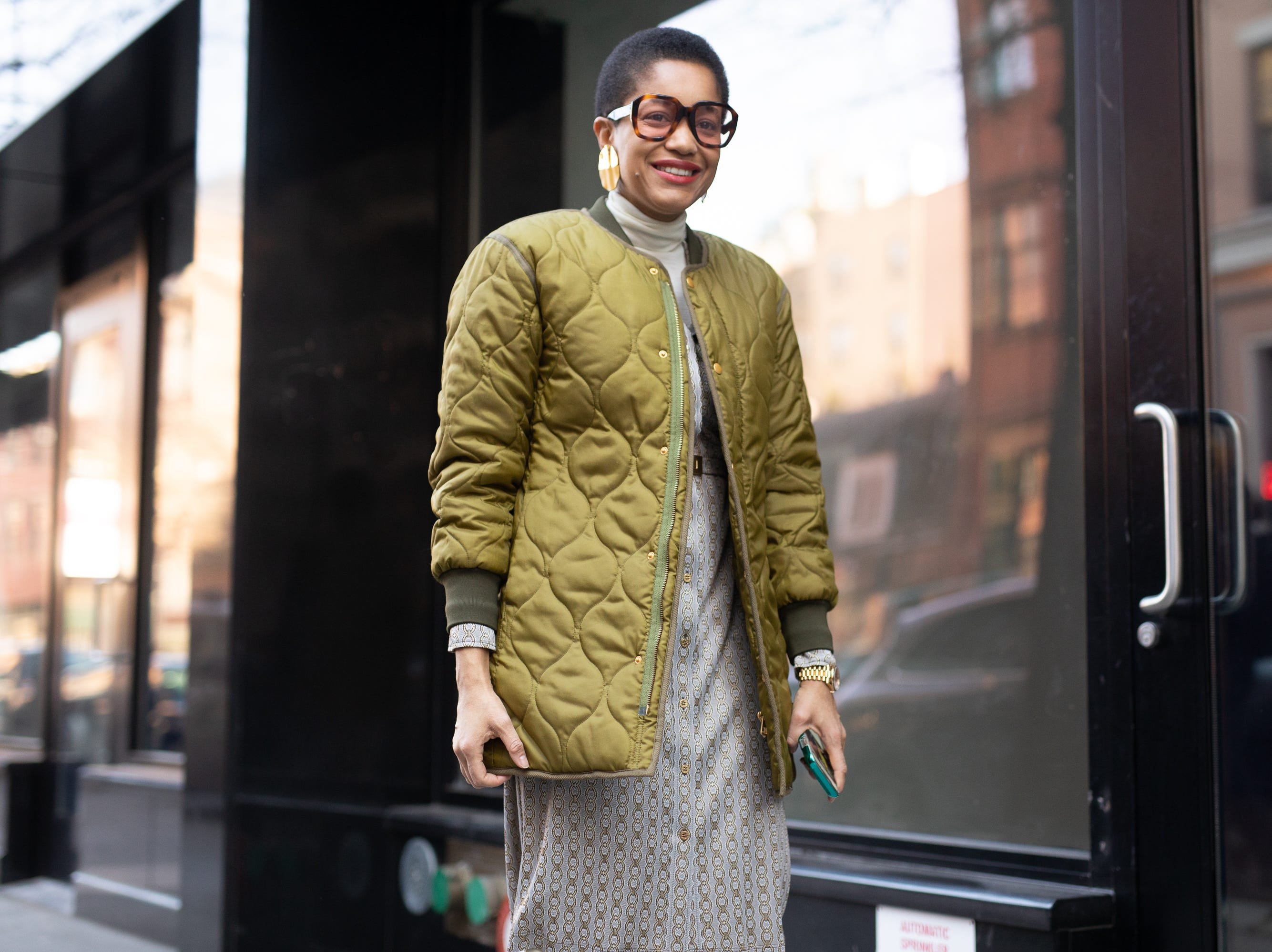 Tamu McPherson is seen on the street during New York Fashion Week AW19 wearing quilted pea green coat with grey dress on February 10, 2019 in New York City.