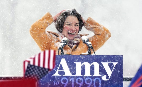 Sen. Amy Klobuchar, D-Minn., wipes snow from her hair after announcing she is running for president, at Boom Island Park, Feb. 10, 2019, in Minneapolis