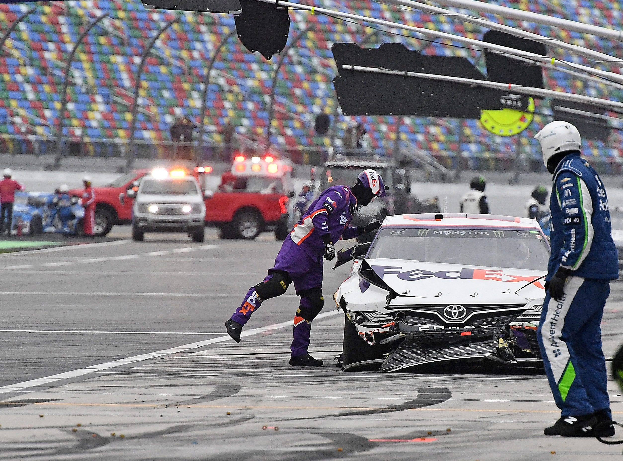 Feb 10: A crew member looks over the damaged car of Denny Hamlin (11) while tow trucks and emergency vehicles attend to other drivers during the Advance Auto Parts Clash at Daytona International Speedway.