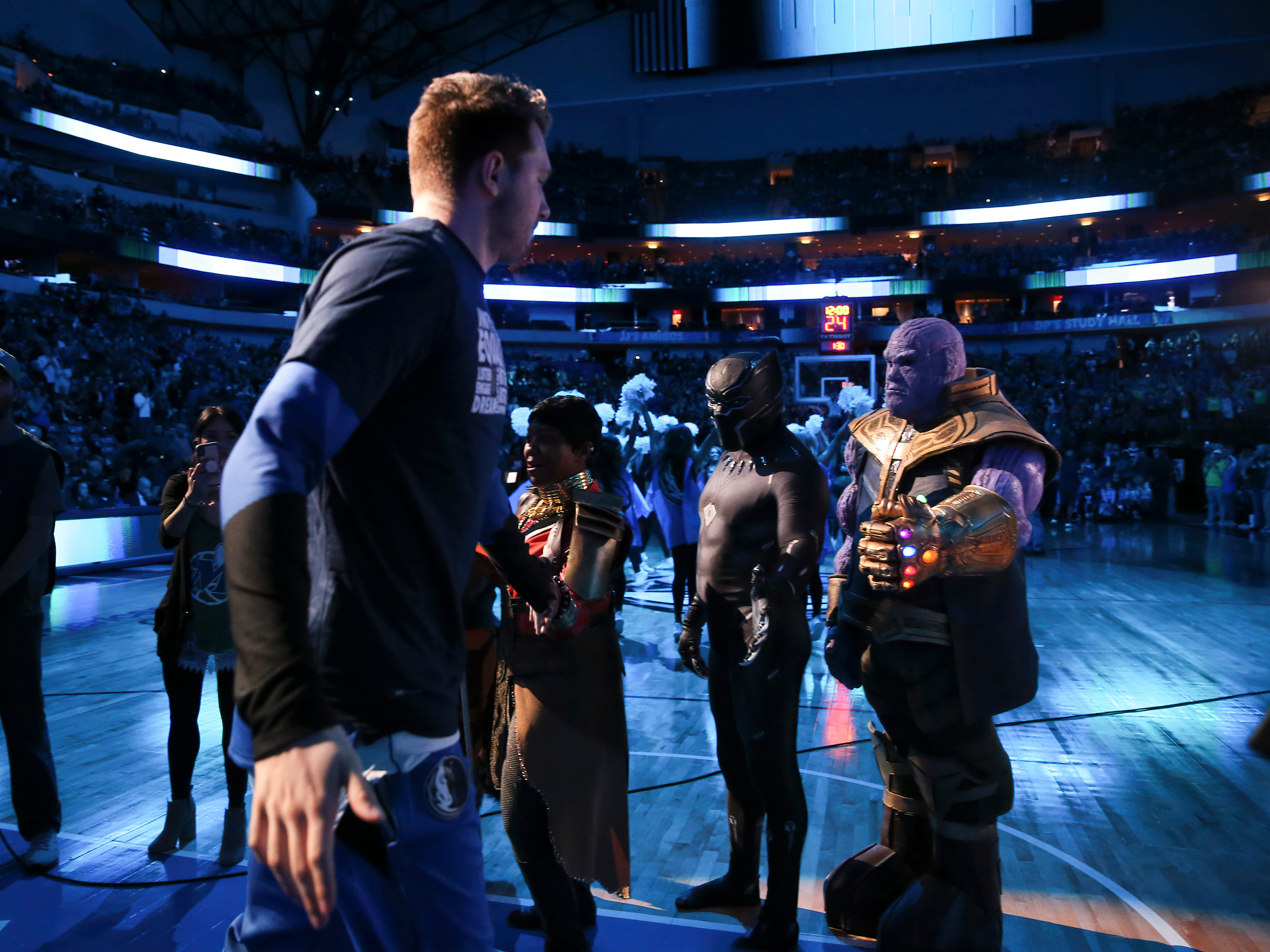 Feb 10: Dallas Mavericks forward Luka Doncic is greeted by comic book character Thanos on Superhero Day before the game against the Portland Trail Blazers at American Airlines Center.