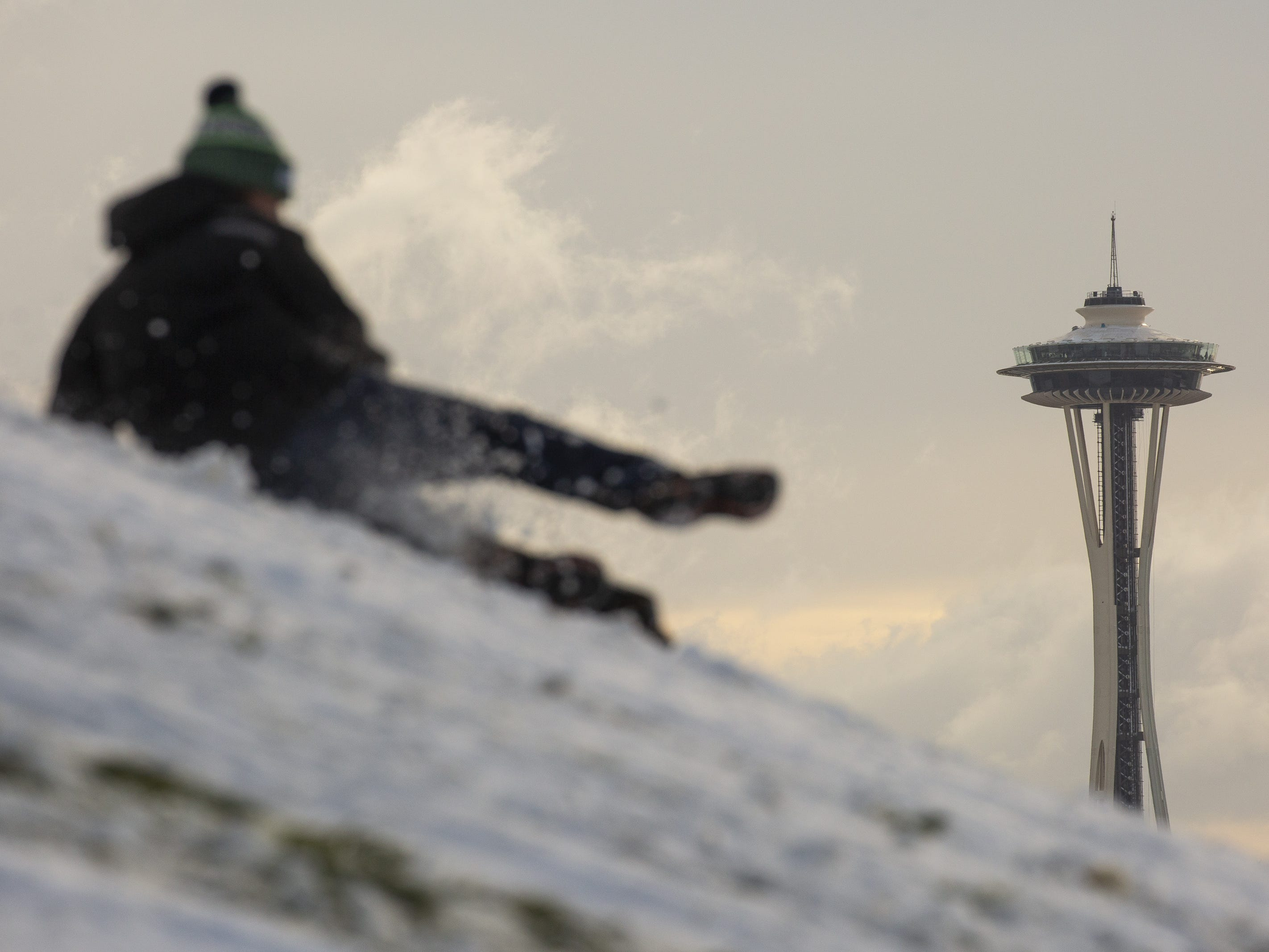 The Space Needle is pictured in the background as a man sleds at Gas Works Park after a large storm blanketed the city with snow on February 9, 2019 in Seattle, Washington.