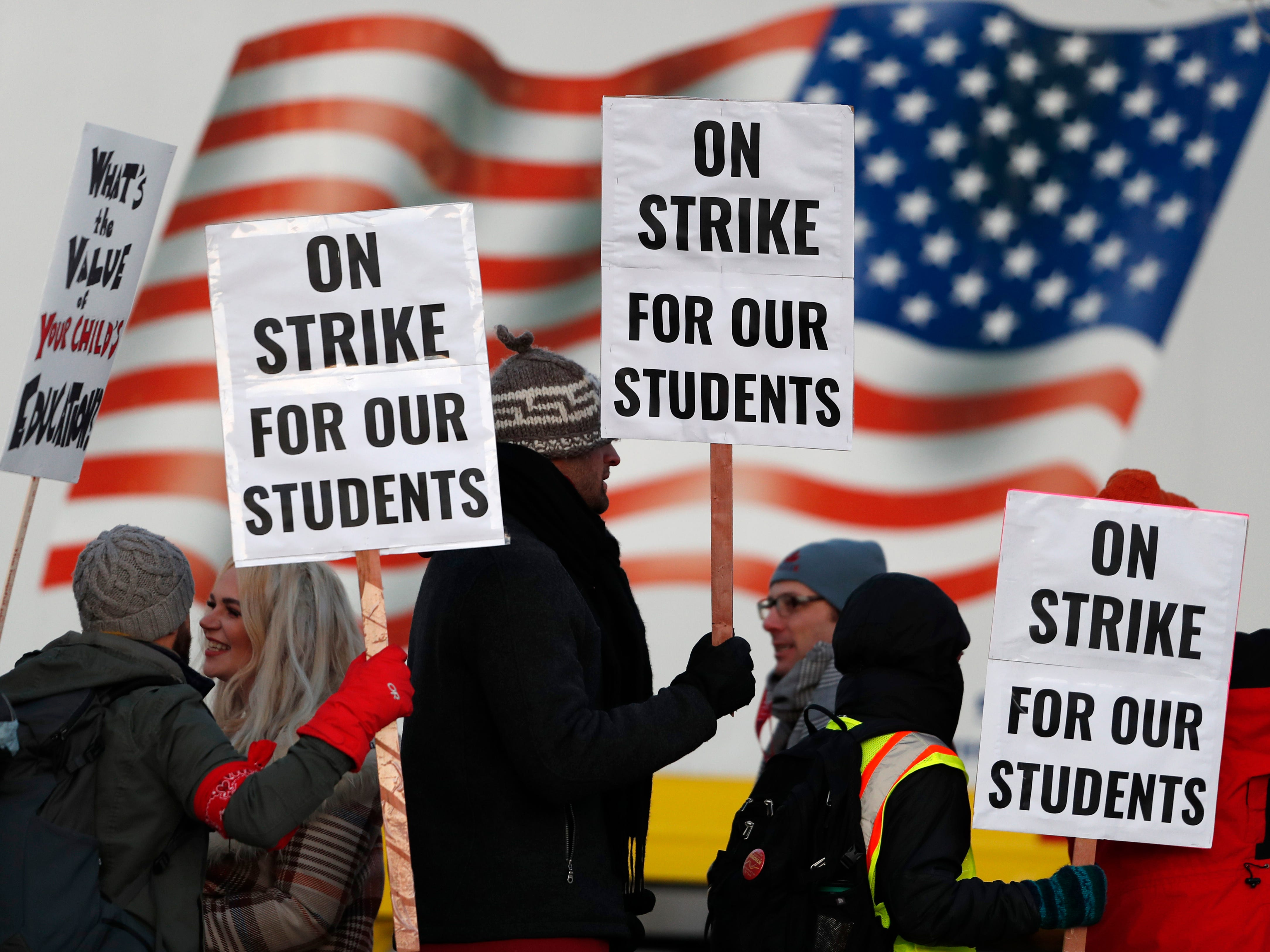 Teachers carry placards as they walk a picket line outside South High School early Monday, Feb. 11, 2019, in Denver. The strike on Monday is the first for teachers in Colorado in 25 years after failed negotiations with the school district over base pay. (AP Photo/David Zalubowski) ORG XMIT: CODZ102