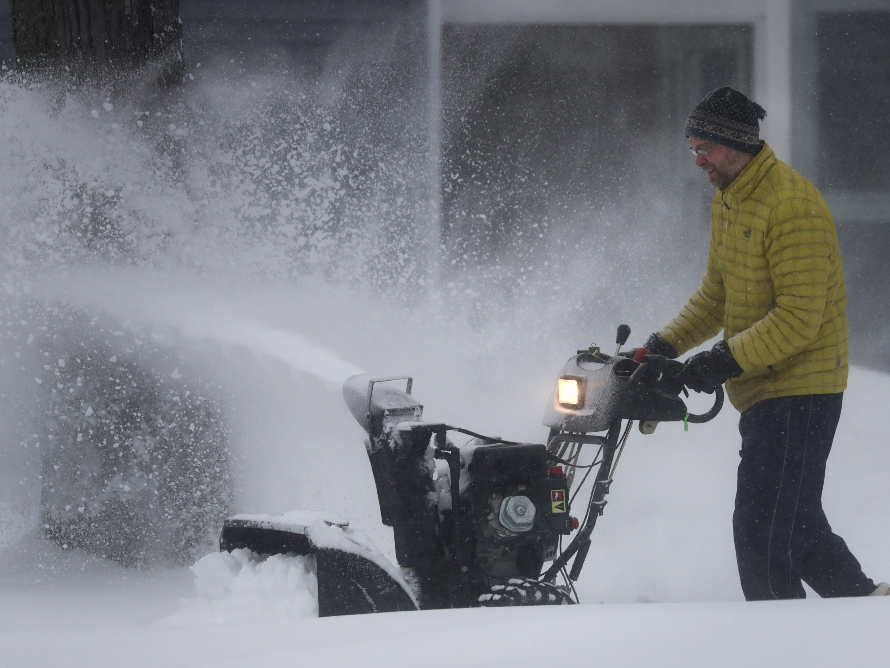 Jeff Clark clears a sidewalk on Tuesday, Feb. 12, 2019, in Appleton, Wis. The latest snow storm to move through the state dropped several inches of snow overnight, 6 to 12 inches are expected by Tuesday evening.