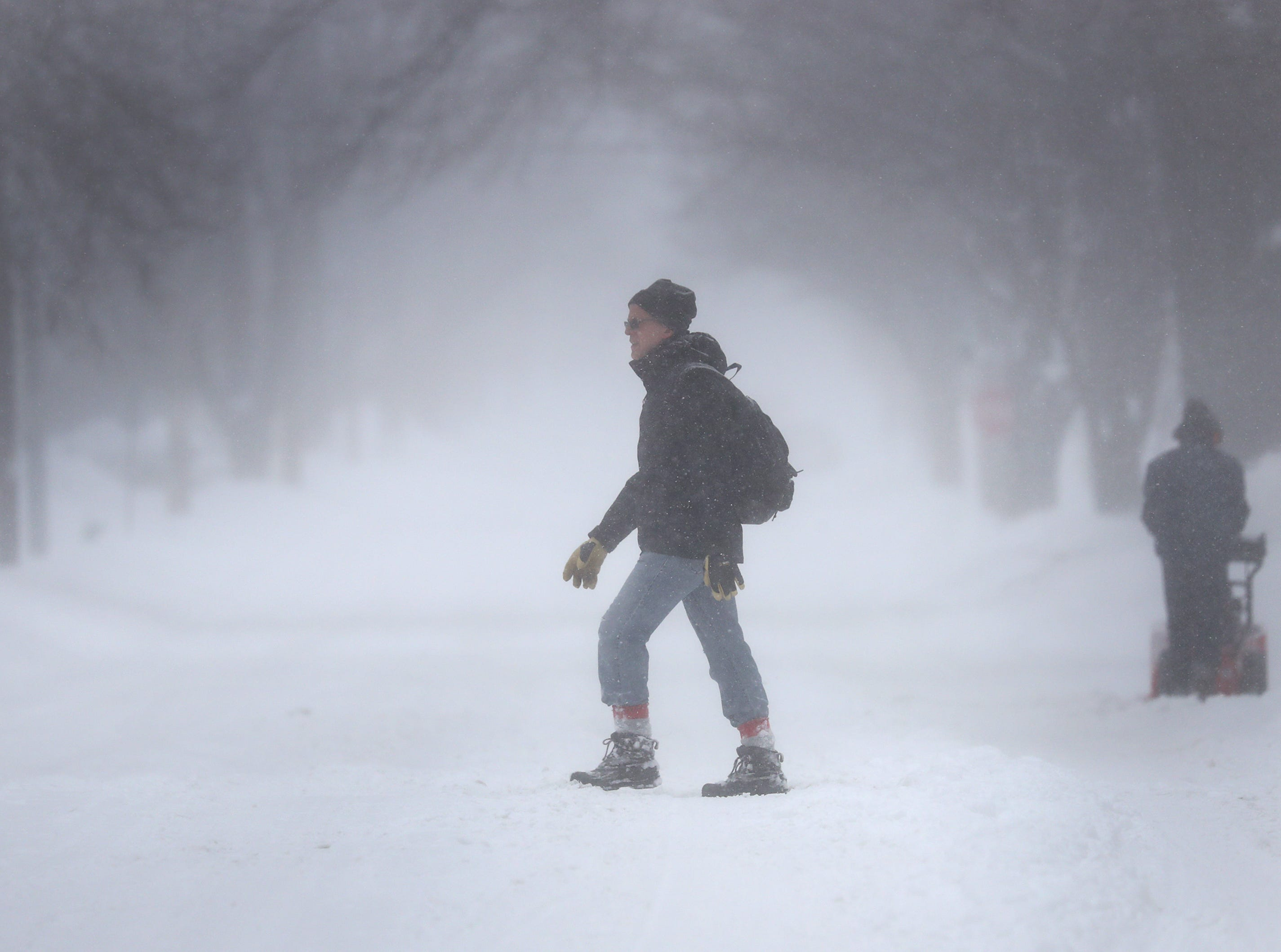 A pedestrian navigates a snow-covered street on Tuesday, Feb. 12, 2019, in Appleton, Wis. The latest snow storm to move through the state dropped several inches of snow overnight, 6 to 12 inches are expected by Tuesday evening.