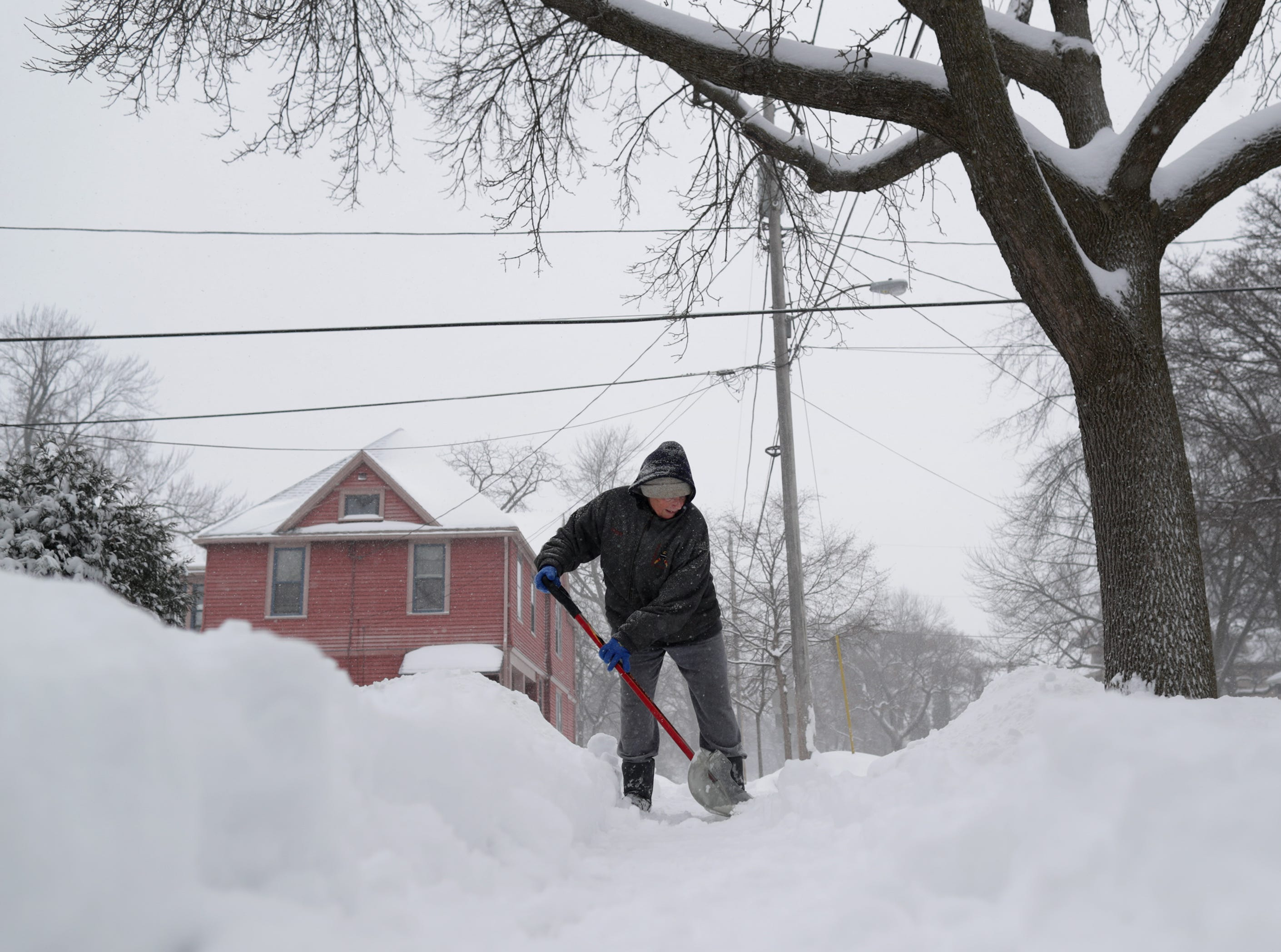 Judy Porter shovels her sidewalk on Tuesday, Feb. 12, 2019, in Appleton, Wis. The latest snow storm to move through the state dropped several inches of snow overnight, 6 to 12 inches are expected by Tuesday evening.
