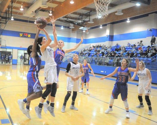 Merkel freshman Alyssa O'Malley goes up for a layup as Coleman's Damara Thomas, left, and Shiean Walters (4) defend.