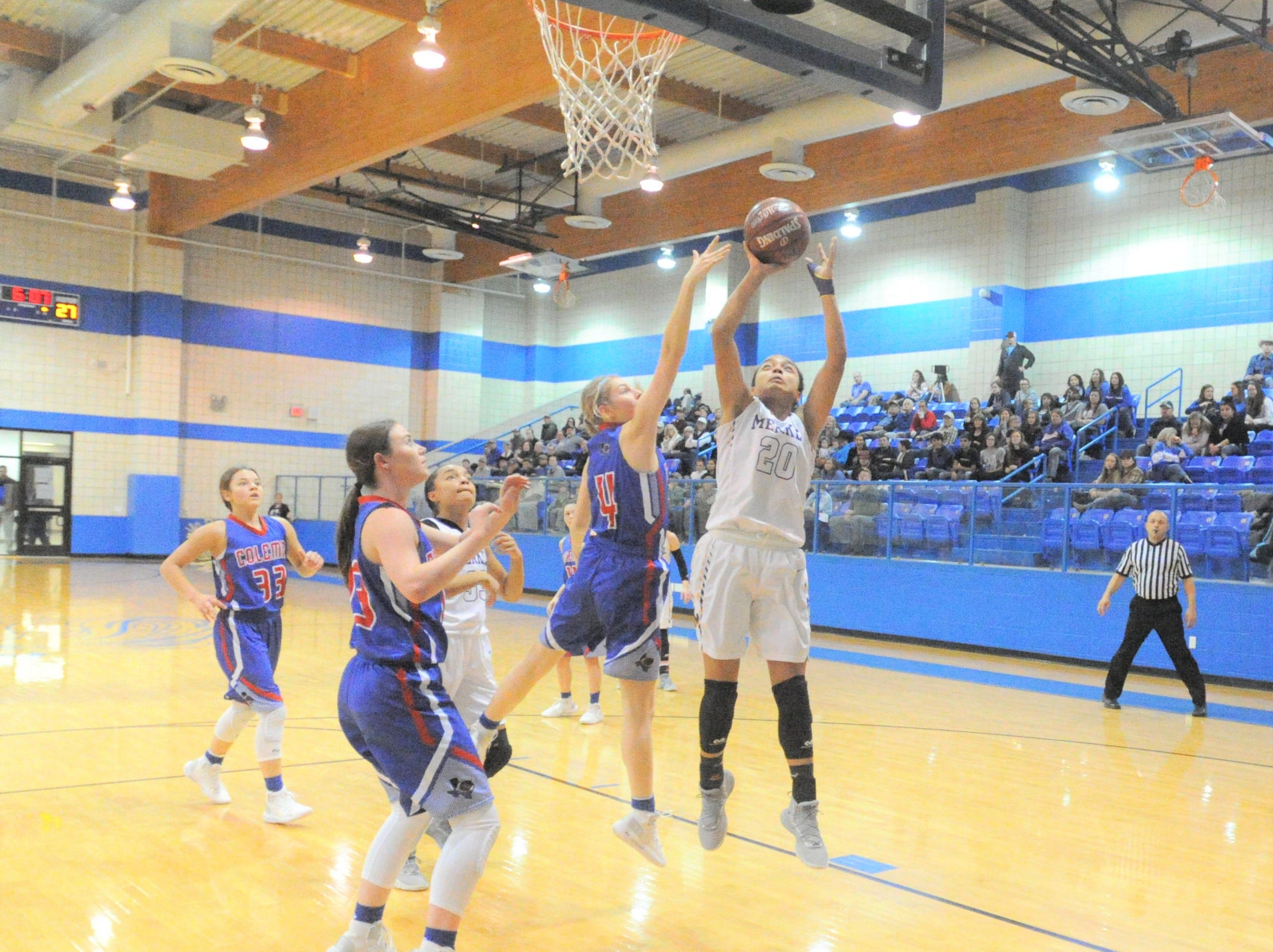 Merkel sophomore Alyssa White (20) scores in the paint in front of Coleman's Abbi Allen (4) in a bi-district playoff at Winters High School on Monday, Feb. 11, 2019.
