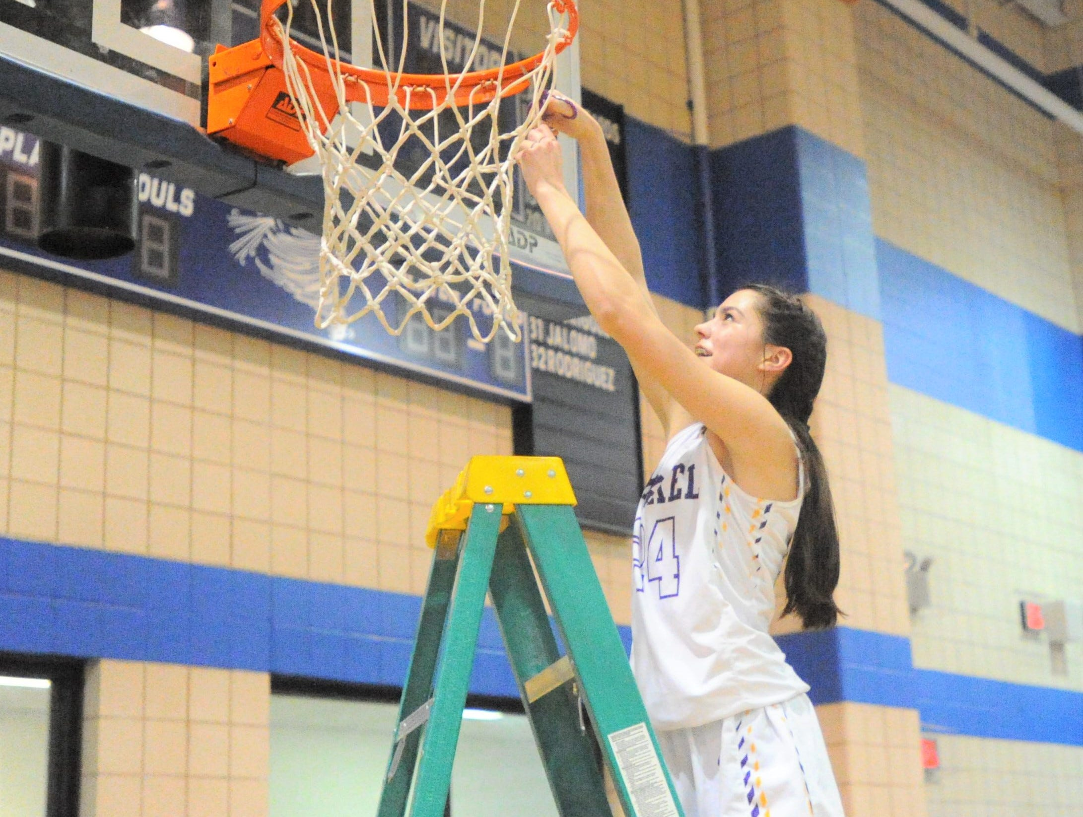 Merkel freshman Alyssa O'Malley cuts a piece of the net at Winters High School on Monday, Feb. 11, 2019, following the Lady Badgers' 49-33 win over Coleman.