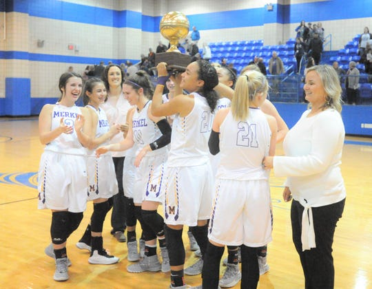 Merkel sophomore Alyssa White (20) holds up the Lady Badgers' bi-district trophy after beating Coleman 49-33 Monday, Feb. 11, 2019, at Winters High School.