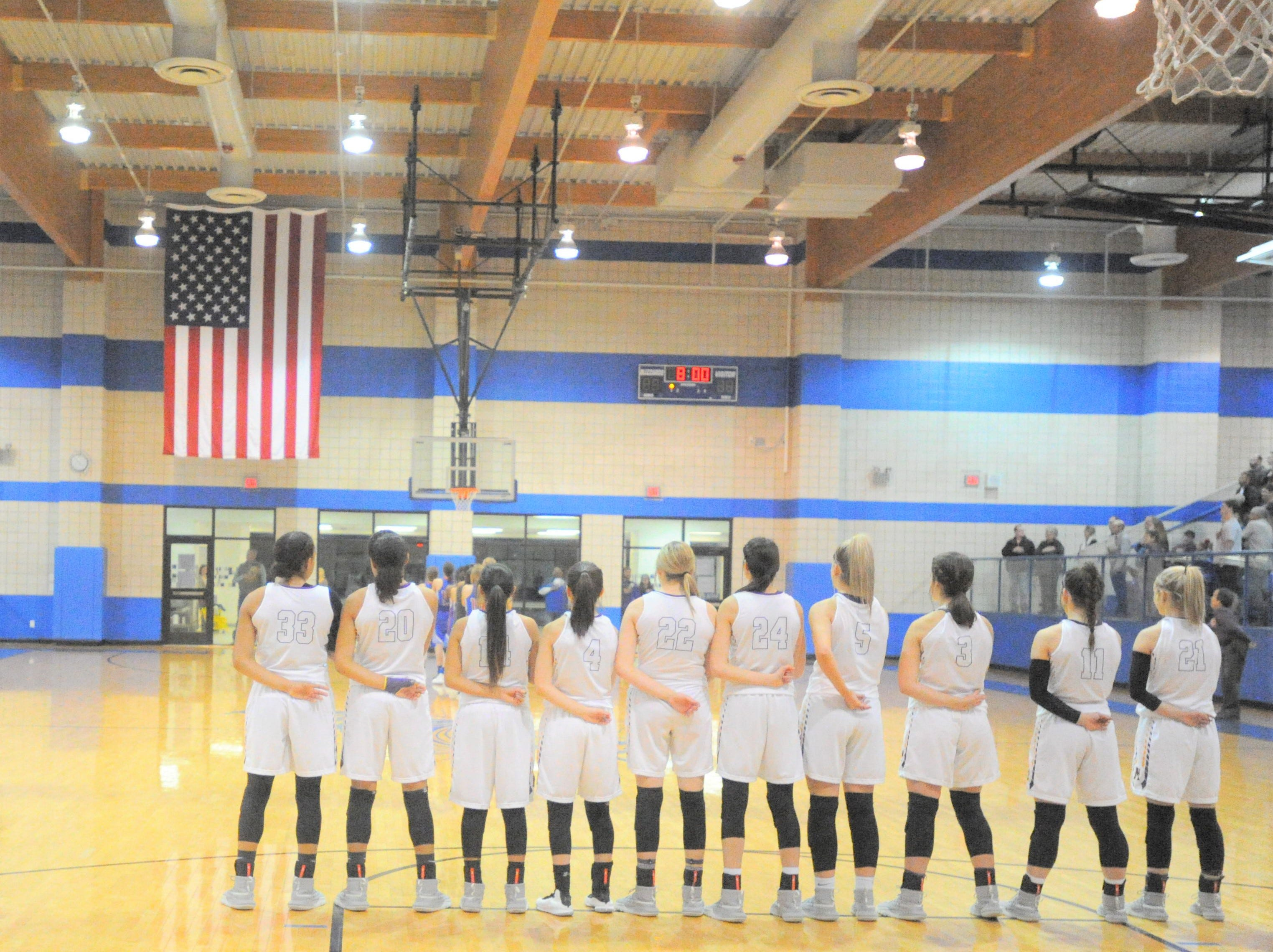 The Merkel girls basketball team stands during the national anthem before its bi-district playoff against Coleman at Winters High School on Monday, Feb. 11, 2019.