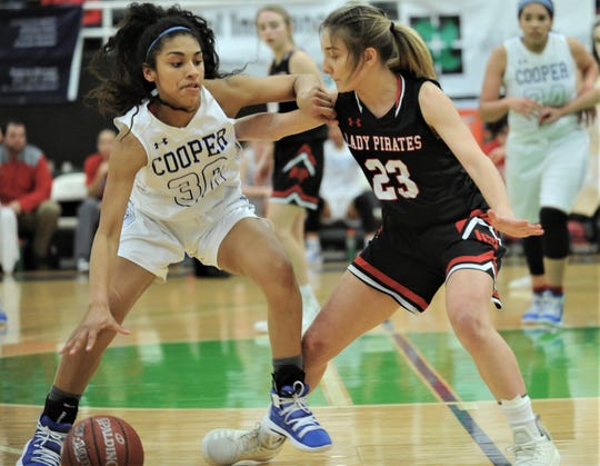 Lubbock-Cooper's Autumn Moore, right, defends against Abilene Cooper's Keiana Kemp as Kemp tries to bring the ball upcourt. Lubbock-Cooper beat the Lady Cougars 63-39 in the Region I-5A bi-district girls basketball playoff game Monday, Feb. 11, 2019, at The Coliseum in Snyder.