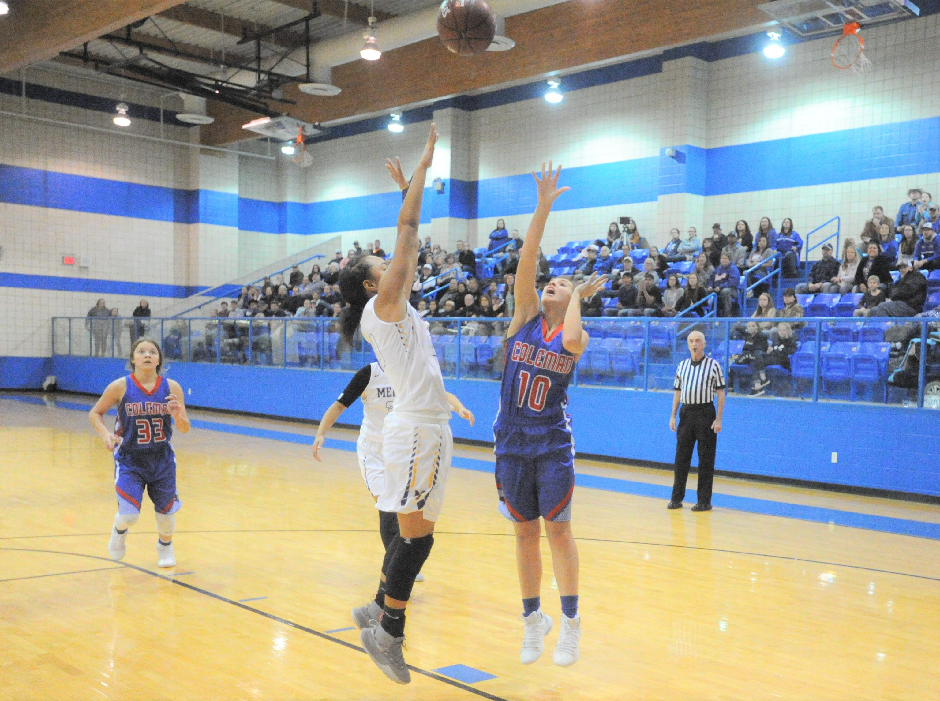 Coleman's Kelly Hale lofts a shot over Merkel's Alyssa White in a bi-district playoff at Winters High School on Monday, Feb. 11, 2019.