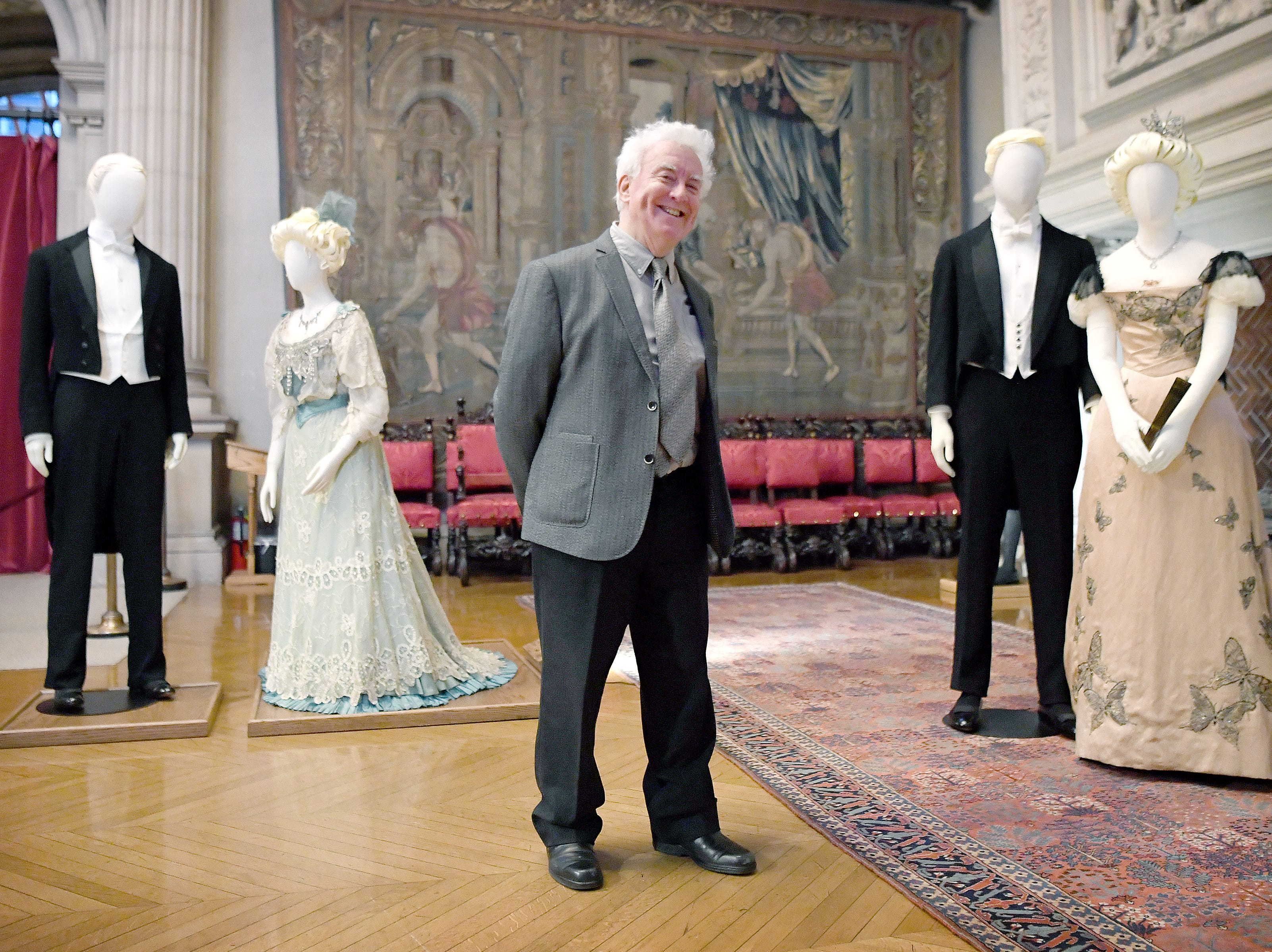"""John Bright, costume designer and owner of Cosprop, London, stands with his creations in the banquet hall of the Biltmore House during a media preview of """"A Vanderbilt House Party, the Gilded Age,"""" on Feb. 7, 2019. Bright and his team designed the clothing displayed in the house from historical photographs of the Vanderbilts and their house guests."""