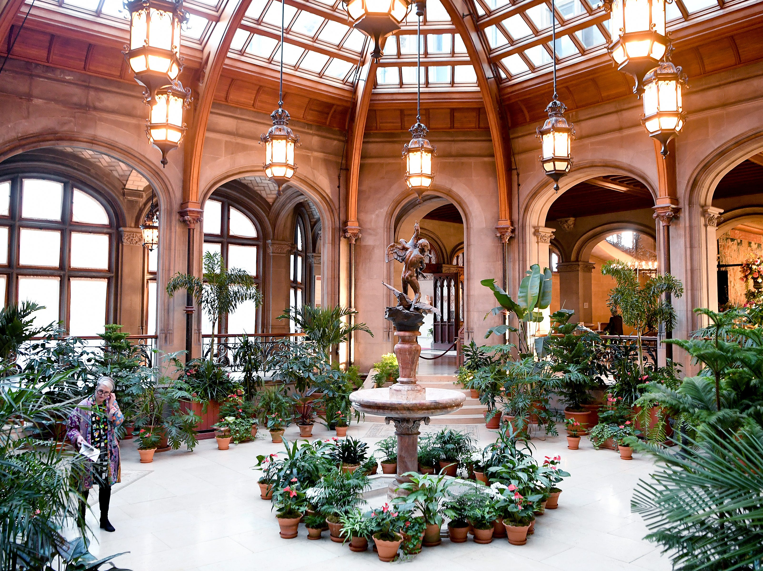 """Stacey Kirby walks through the Winter Garden of the Biltmore House as she listens to an audio tour during a a preview of """"A Vanderbilt House Party, the Gilded Age,"""" on Feb. 7, 2019."""