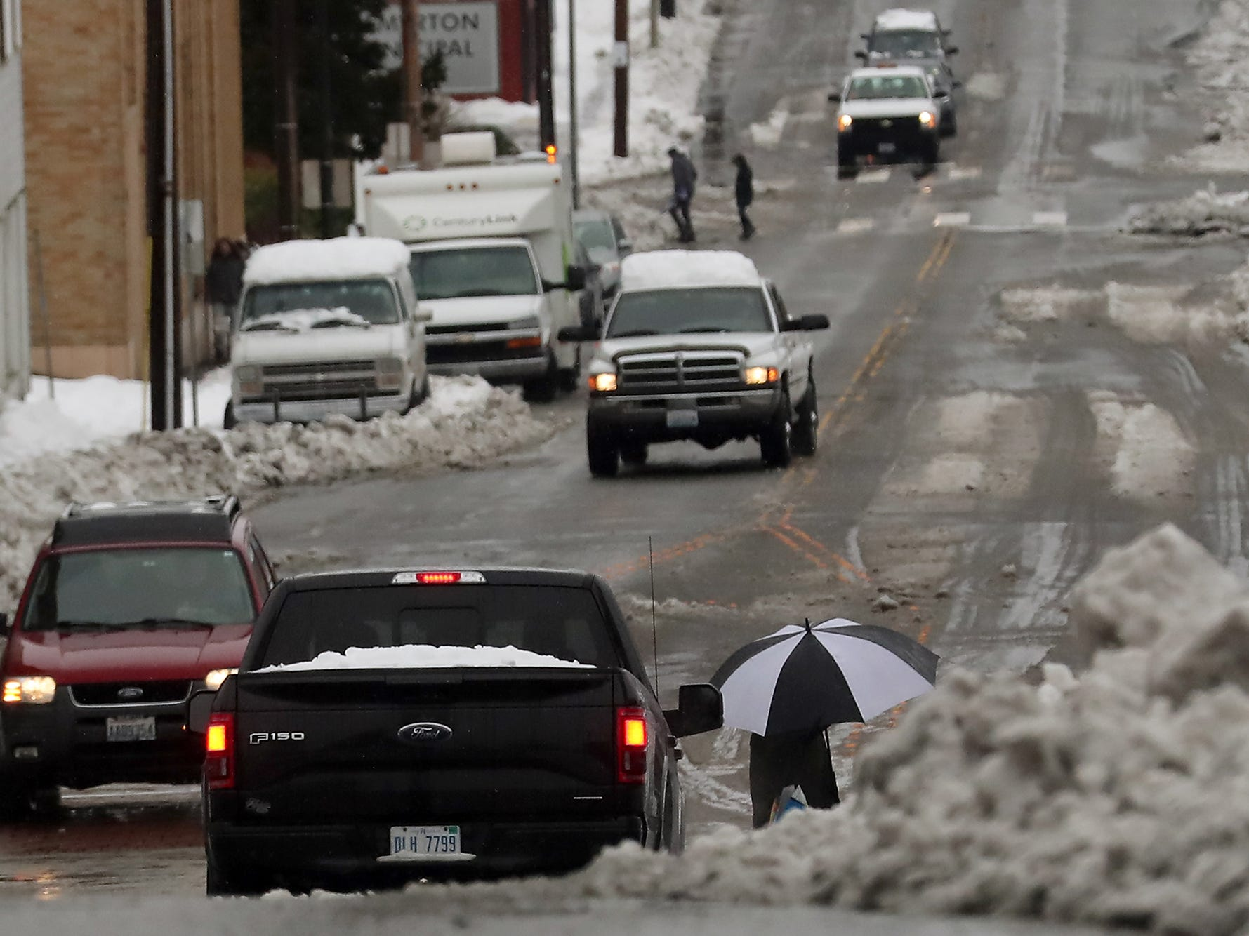 An umbrella is framed by cars and a pile of snow as a pedestrian crosses 6th Street at Pacific Avenue in downtown Bremerton on Tuesday, February 12. 2019.