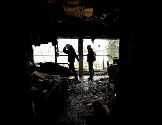 Katrina Kane and daughter Max Jung are silhouetted against the broken out windows as they look over the damage to their home at Thunderbird Apartments in Bremerton on Tuesday.