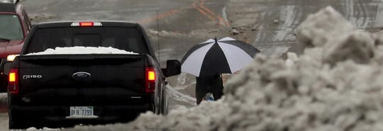 An umbrella is framed by cars and a pile of snow as a pedestrian crosses Sixth Street at Pacific Avenue in downtown Bremerton on Tuesday.