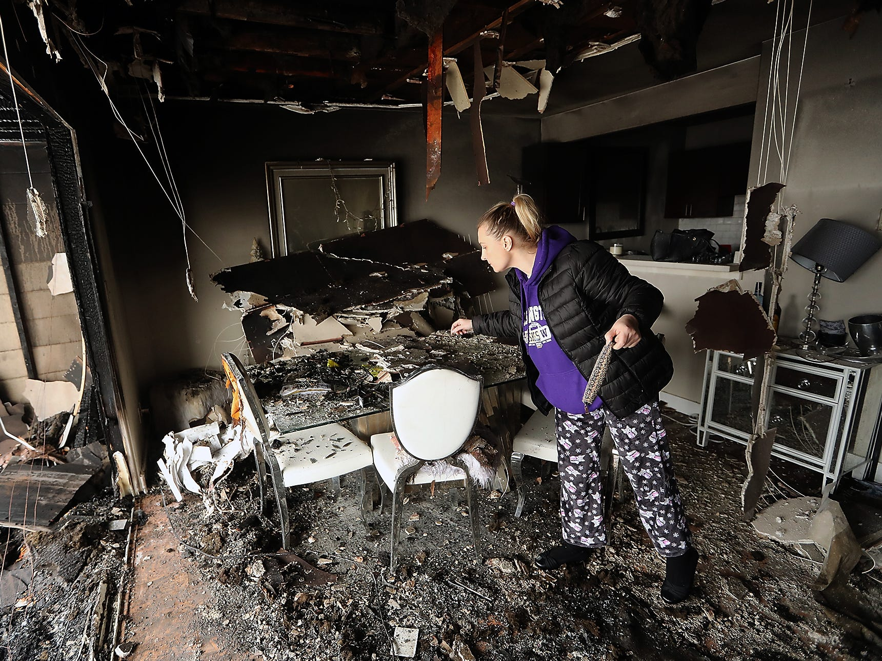 Katrina Kane looks for anything salvageable on the dining room table of her home at Thunderbird Apartments in Bremerton on Tuesday, February 12. 2019. An early morning fire on Monday displaced residents and has made the building unlivable.