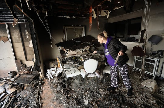 Katrina Kane looks for anything salvageable on the dining room table of her home at Thunderbird Apartments in Bremerton on Tuesday. An early morning fire on Tuesday displaced residents.