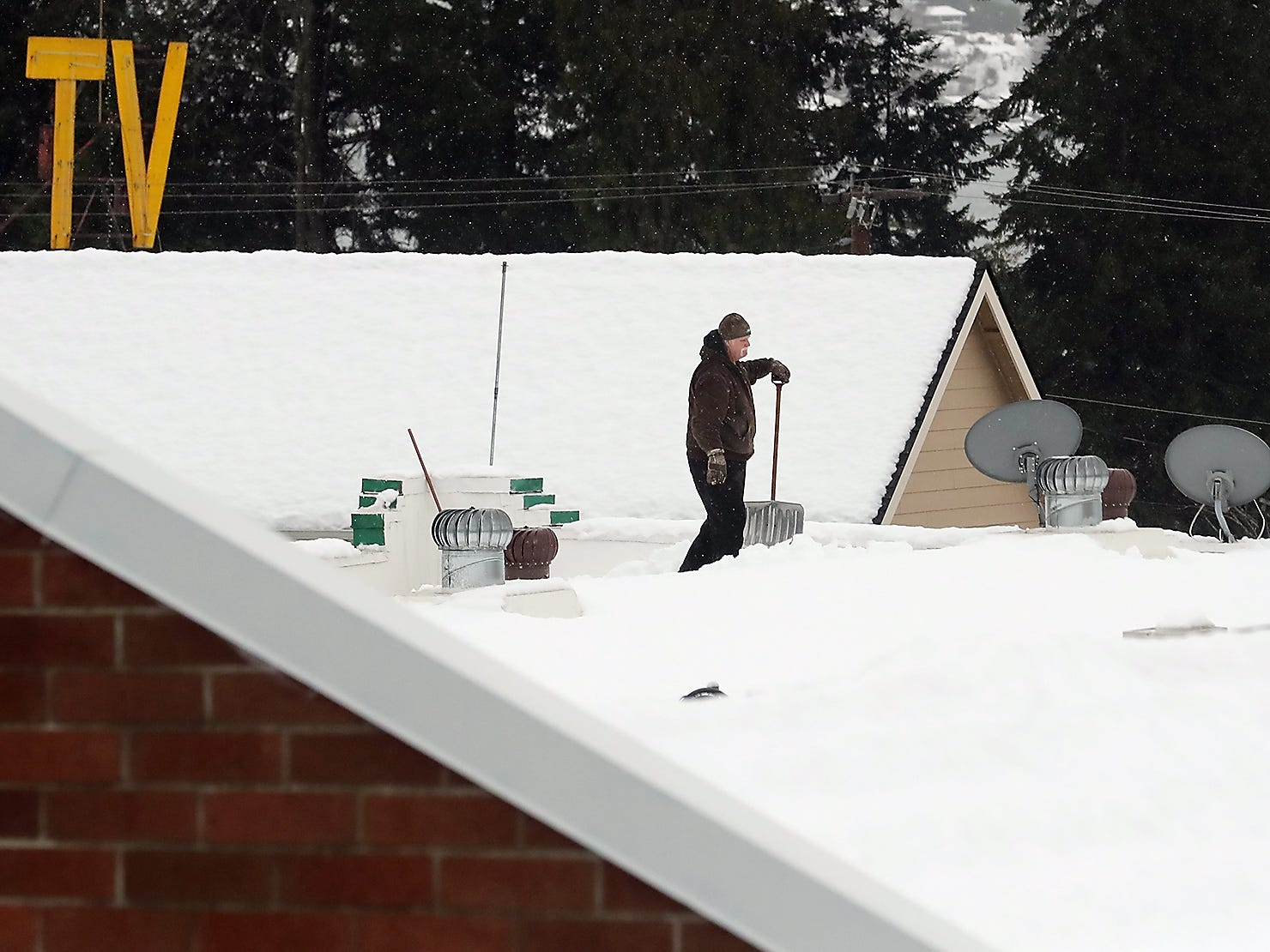 A person shovels the heavy snow off the roof of the R K Mart in Manette  on Tuesday, February 12. 2019.