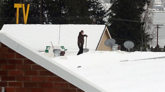A person shovels the heavy snow off the roof of the R K Mart in Manette on Tuesday.