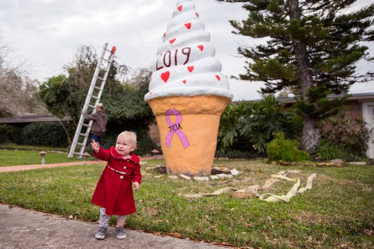 Eloise Kingsbury, 16 months, takes her first and last photo in front of the ice cream cone on Wilshire Place in the Lamar Park neighborhood as its prepared to be moved on Tuesday, February 12, 2019. The ice cream cone has become a well-known Corpus Christi landmark as the late Jennifer Hawn had the cone placed in her yard in 1998 and began the tradition of painting the cone for various holidays and seasons.