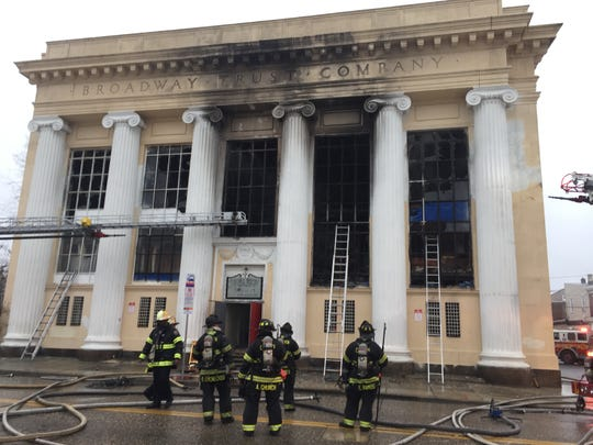 Firefighters stand outside the Broadway Trust Company building in Camden as others douse hot spots inside the structure.