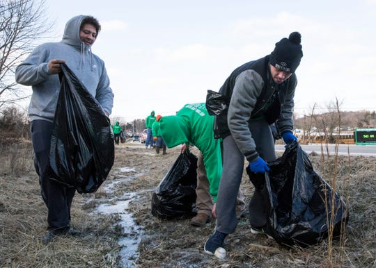 Huntington senior wrestler Cody Thomas attempts to loosen a baseball frozen to the ground on the side of the road Saturday morning as he and several members of the Huntington wrestling team clean trash from the side of OH-772.