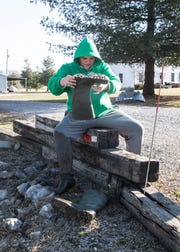 Conner Temple empties debris stuck inside his boot Saturday morning as he finishes up cleaning trash from the side of the road. Temple and several of his fellow wrestlers volunteered to spend their Saturday morning cleaning up OH-772 near Huntington High School.
