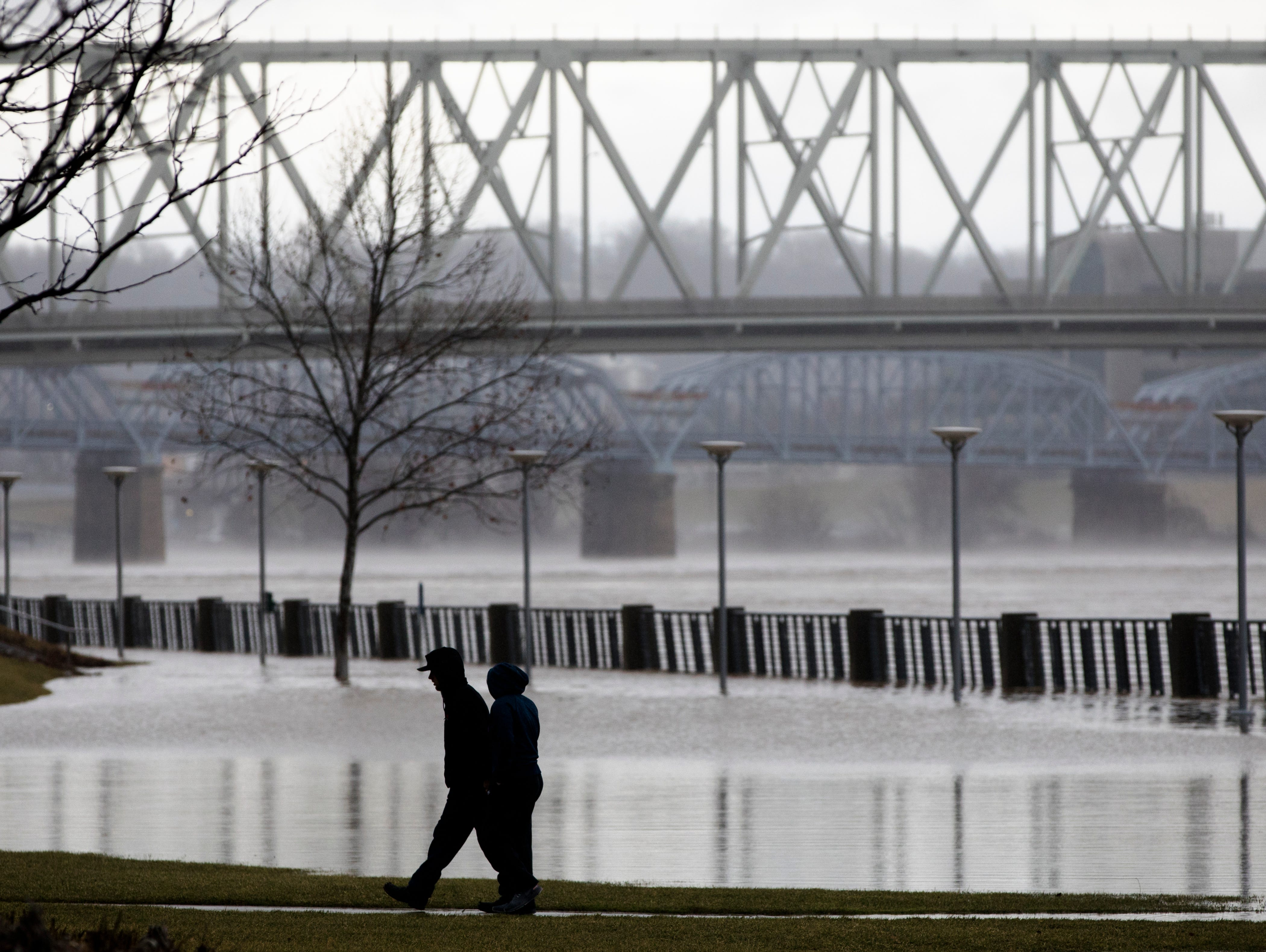 People walk Smale Riverfront Park in Cincinnati on Tuesday, Feb. 12, 2019. The Ohio River is expected to crest at 56.3 feet at 1 a.m. Wednesday, Feb. 13.