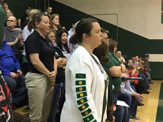 Teachers at Silver Grove Independent School who have no guarantee of a job if a merger with Campbell County Schools is approved stand at the request of a parent Feb. 11 thanking them for their work with students during a board of education meeting in the gym.