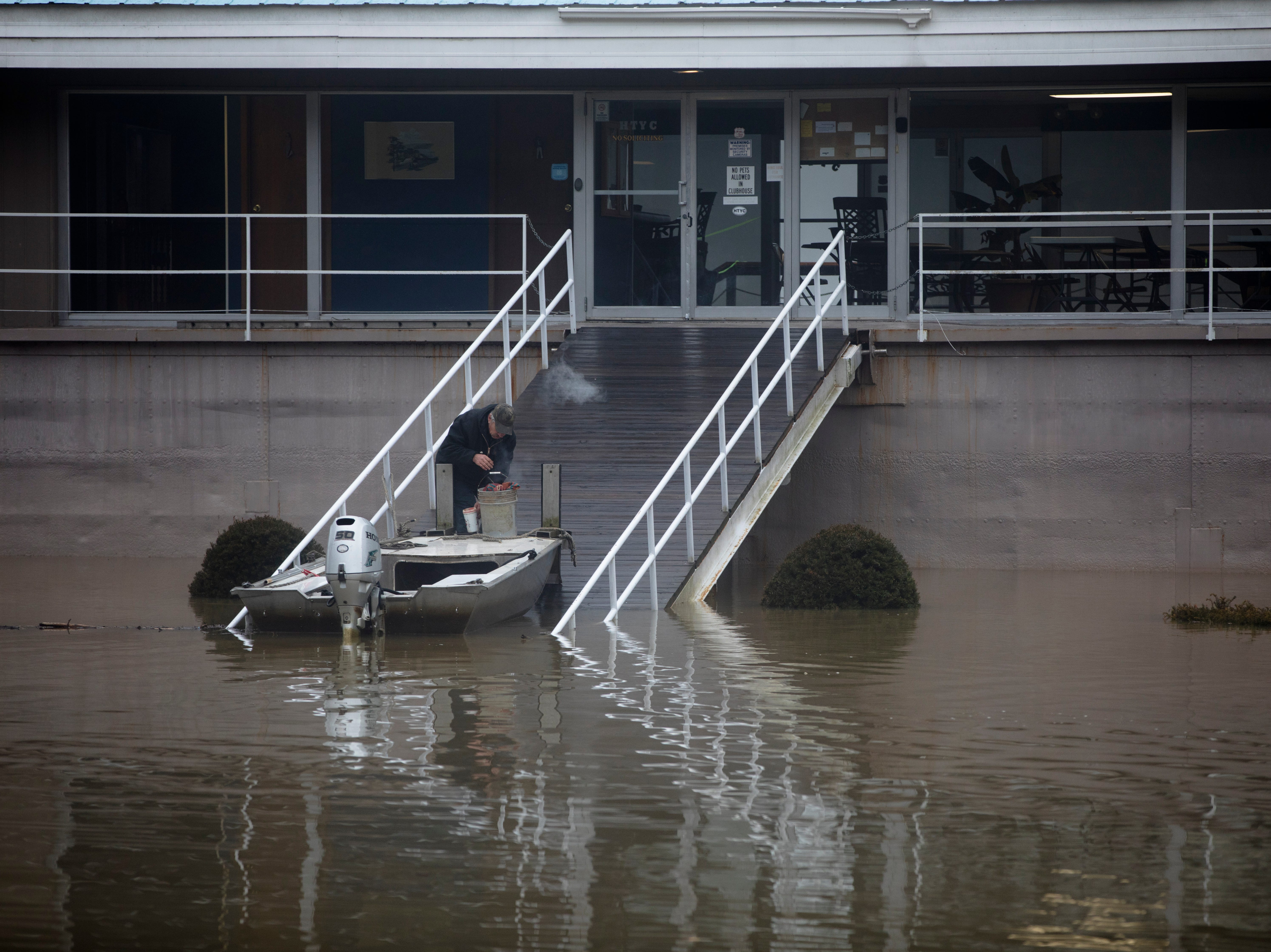 A man parks a boat in the parking lot of the Harbor Towne Yacht Club on Tuesday, Feb. 12, 2019.