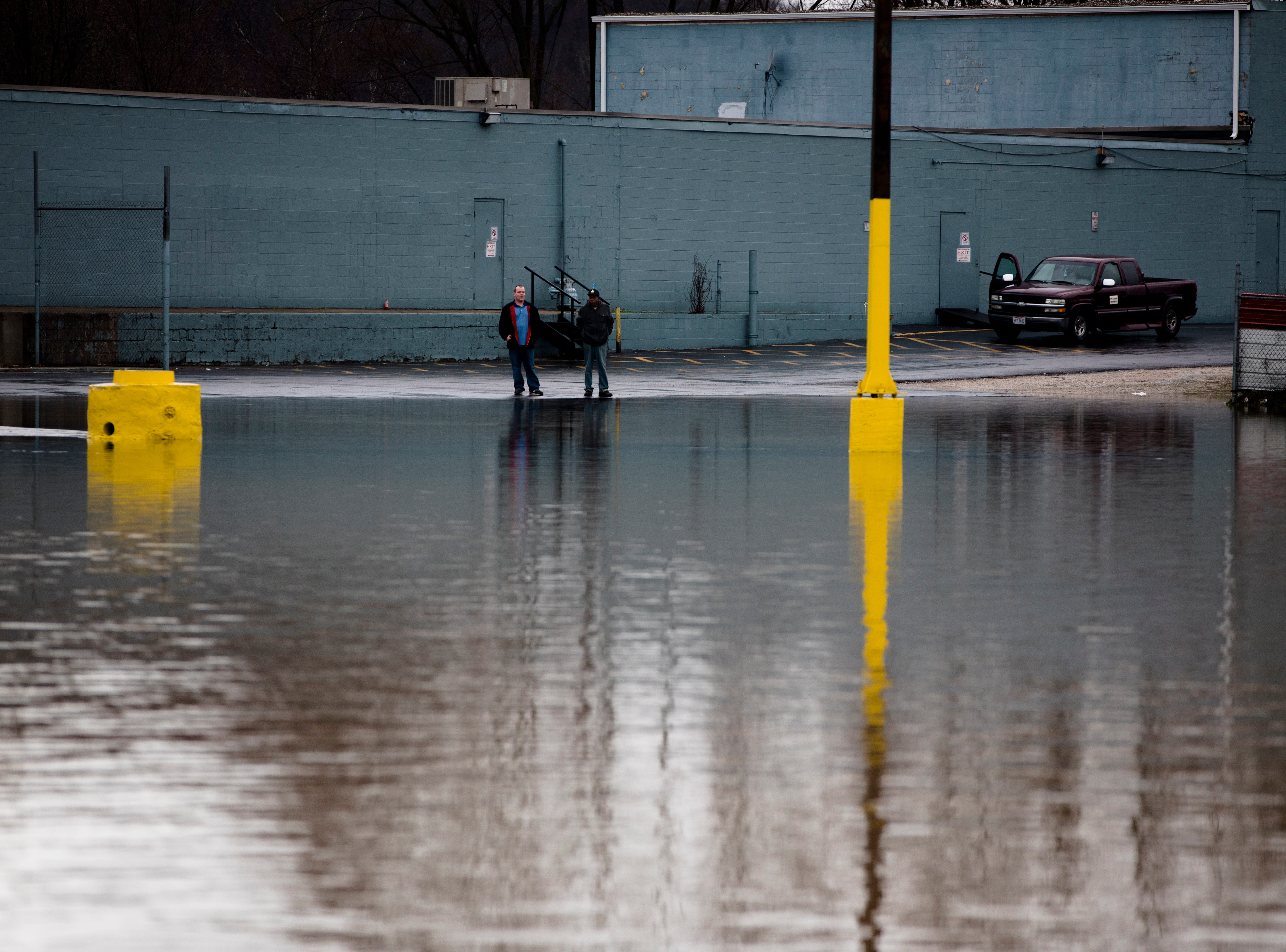 People look across a flooded parking lot on Kellogg Avenue on Tuesday, Feb. 12, 2019.