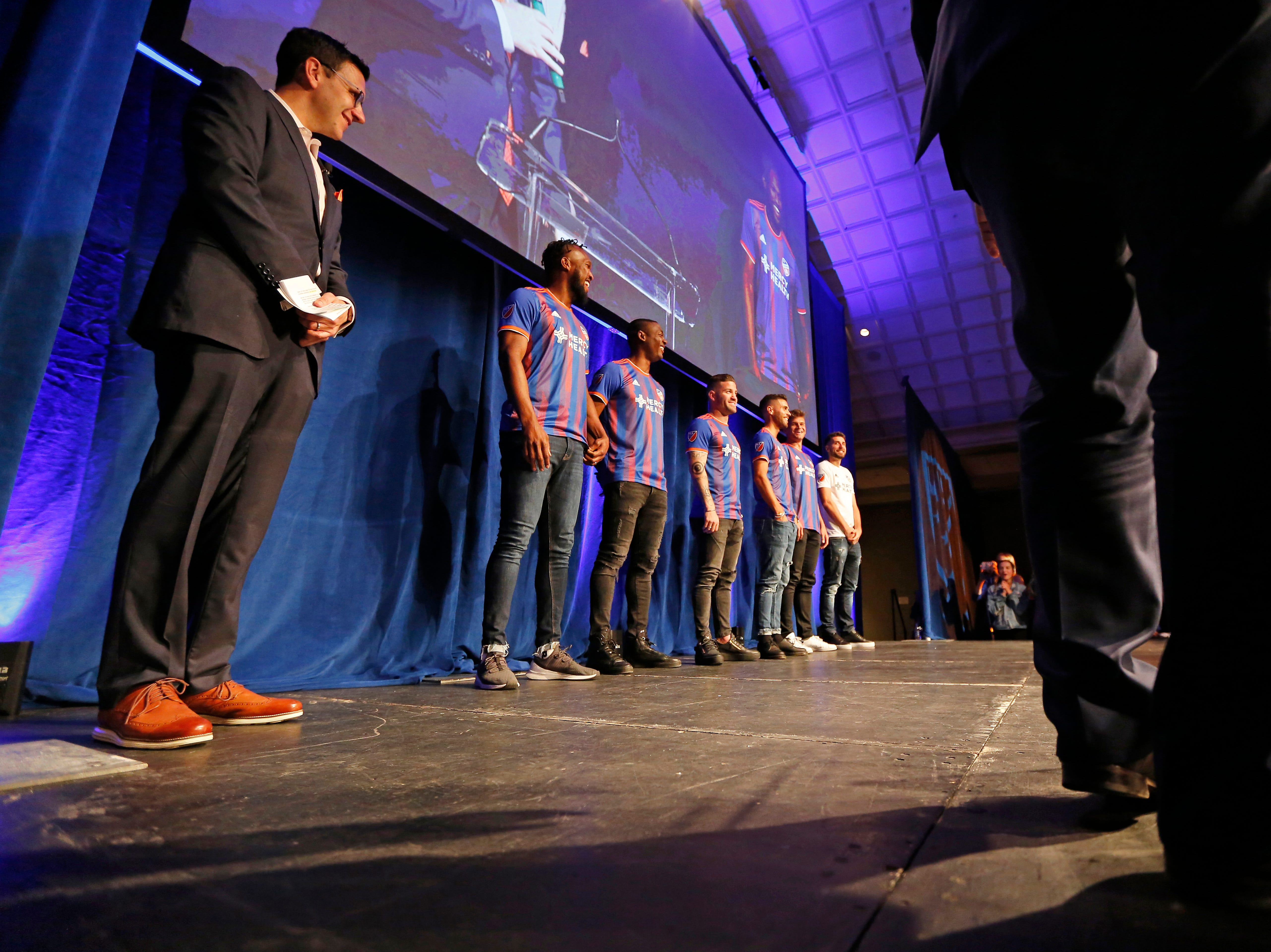 Player representatives take the stage in the new jerseys during an event to unveil FC Cincinnati's jersey for the team's inaugural season in Major League Soccer at the Music Hall Ballroom in the Over-the-Rhine neighborhood of Cincinnati on Monday, Feb. 11, 2019.