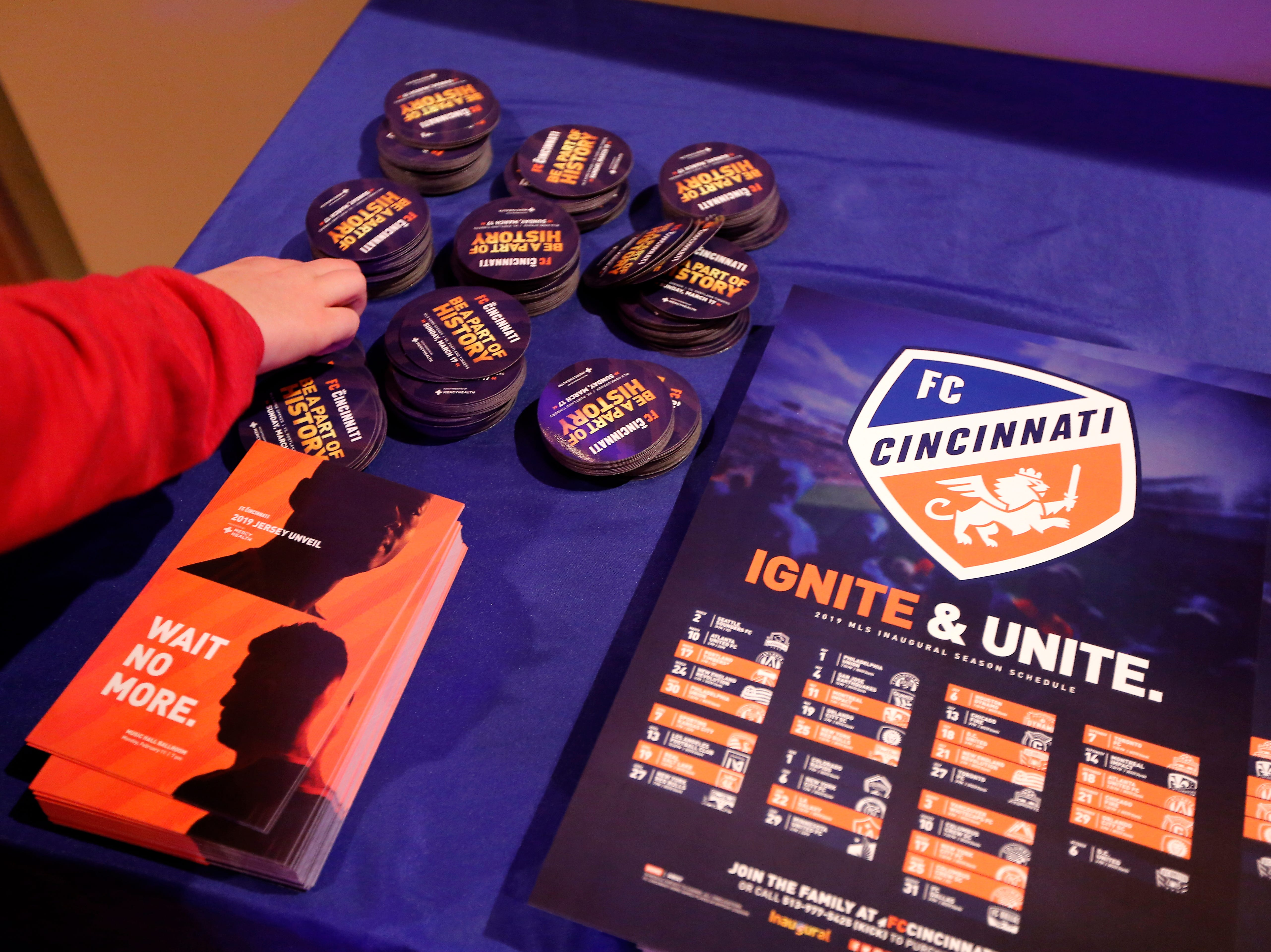 Fans grab flyers and posters during an event to unveil FC Cincinnati's jersey for the team's inaugural season in Major League Soccer at the Music Hall Ballroom in the Over-the-Rhine neighborhood of Cincinnati on Monday, Feb. 11, 2019.