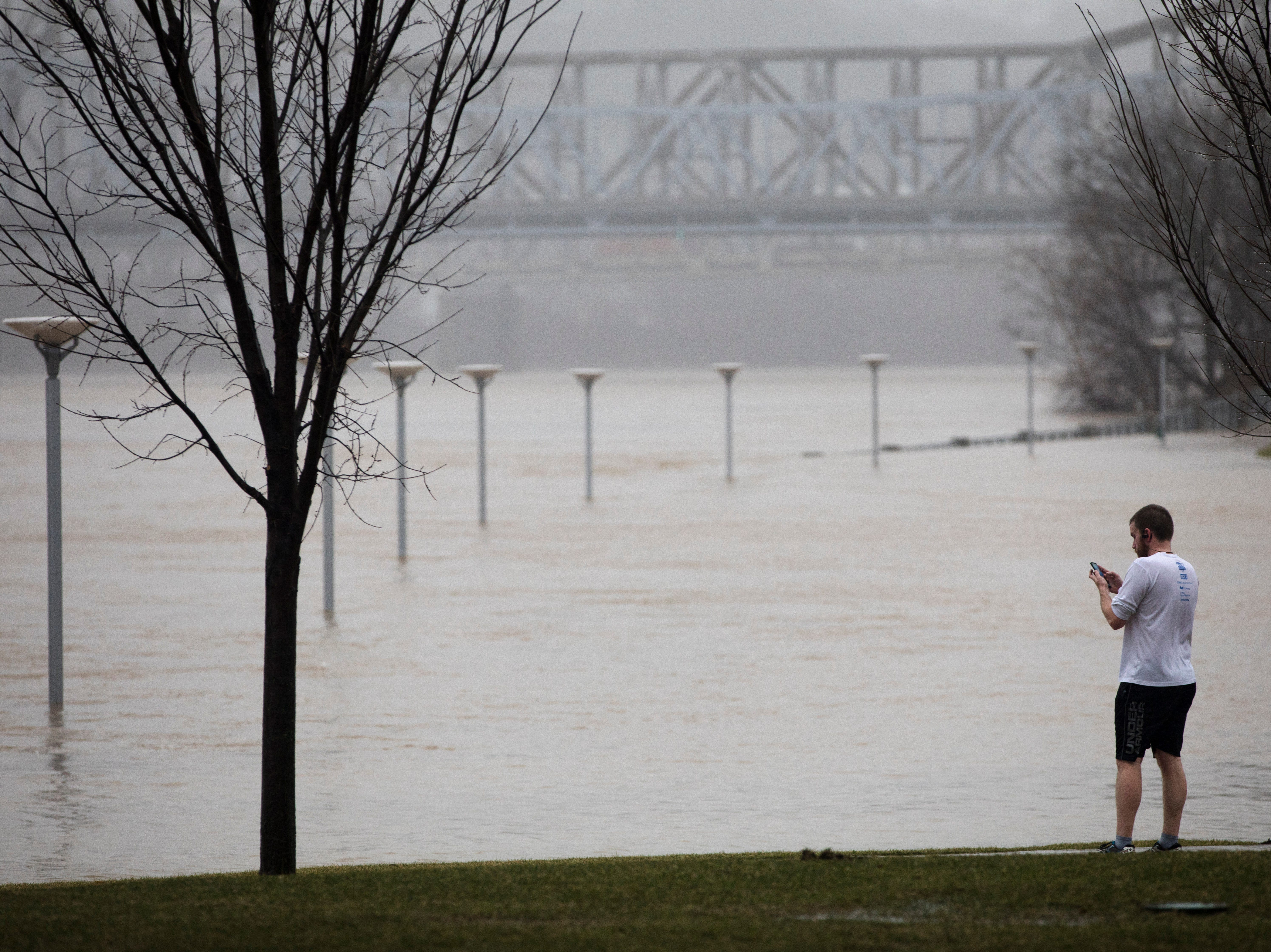 A runner stops to take a photograph at Smale Riverfront Park in Cincinnati on Tuesday, Feb. 12, 2019. The Ohio River is expected to crest at 56.3 feet at 1 a.m. Wednesday, Feb. 13.