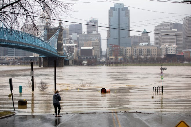 A woman looks out at the Ohio at the intersection at Riverside Place and Ben Bernstein Place in Covington on Tuesday, Feb. 12, 2019. The Ohio River is expected to crest at 56.3 feet at 1 a.m. Wednesday, Feb. 13.