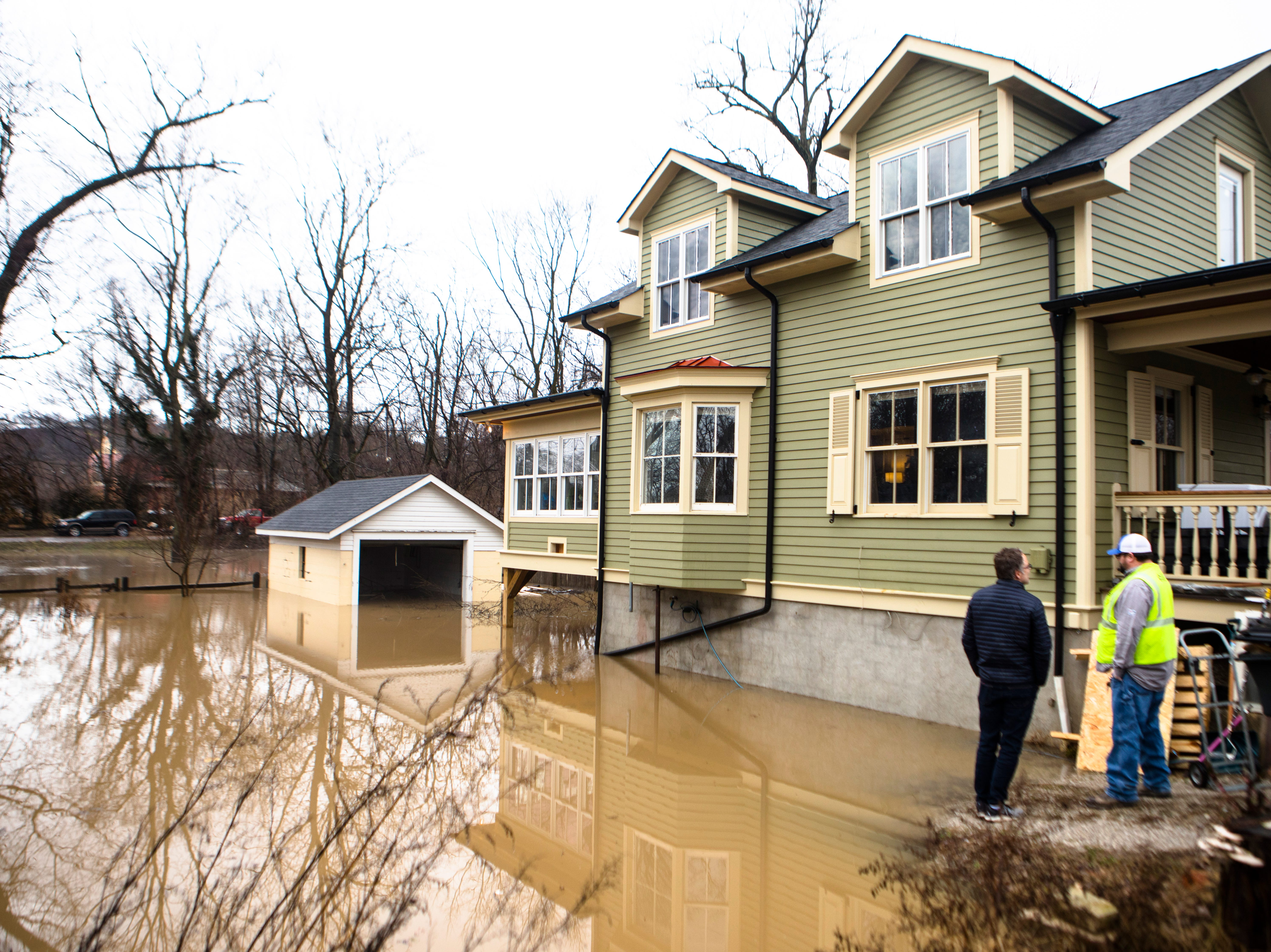 A resident looks at his flooded property with a Duke Energy employee on Strader Avenue in Hyde Park on Tuesday, Feb. 12, 2019.