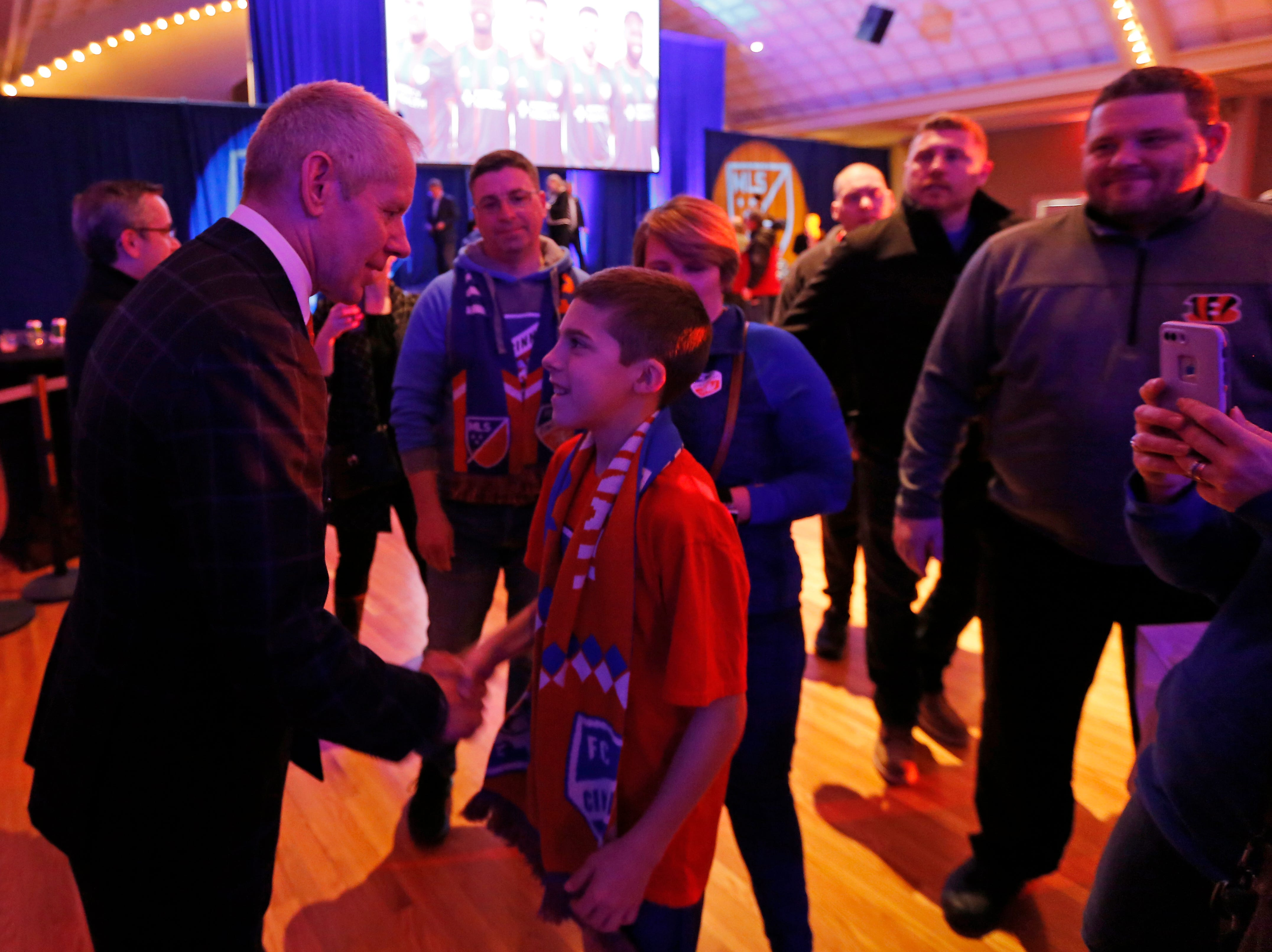 Team owner Carl Lindner III shakes hands with Gaven Johnson, 12, of Harrison, during an event to unveil FC Cincinnati's jersey for the team's inaugural season in Major League Soccer at the Music Hall Ballroom in the Over-the-Rhine neighborhood of Cincinnati on Monday, Feb. 11, 2019.