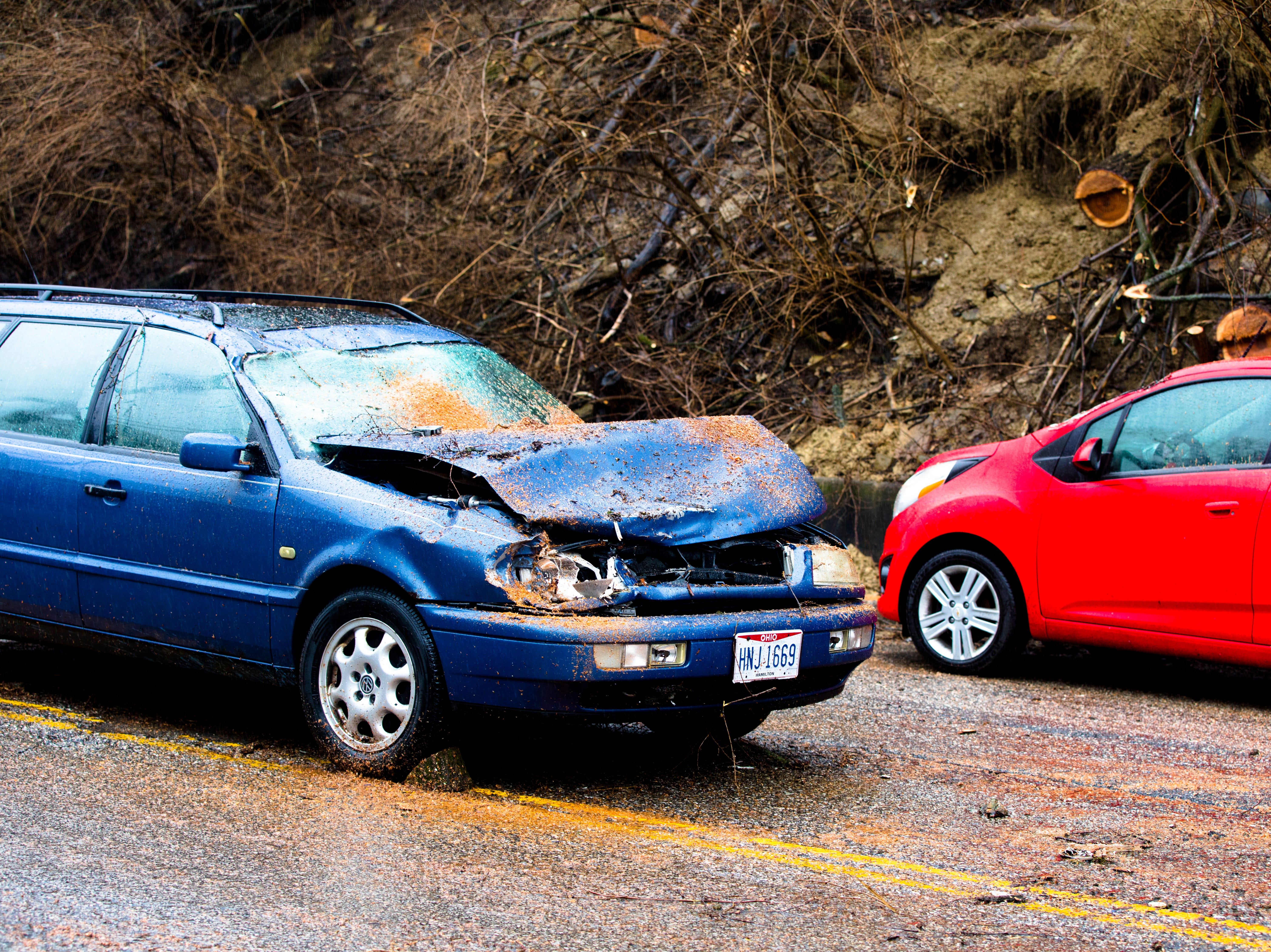 A car sits on Straight Street in-between Luna and McMicken Avenue after being hit by a tree in a landslide in Cincinnati on Tuesday, Feb. 12, 2019. The Ohio River is expected to crest at 56.3 feet at 1 a.m. Wednesday, Feb. 13.