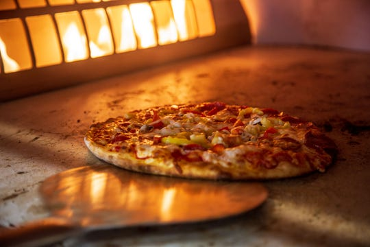 A pizza cooks in the wood fire oven at the new Hy-Vee Fast and Fresh combination gas and grocery store in Altoona Tuesday, Feb. 12, 2019.