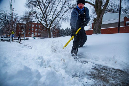Matthew Lemons with Iowa Contractors clears a fresh coat of snow from the sidewalk in front of Friends Church Tuesday, Feb. 12, 2019.