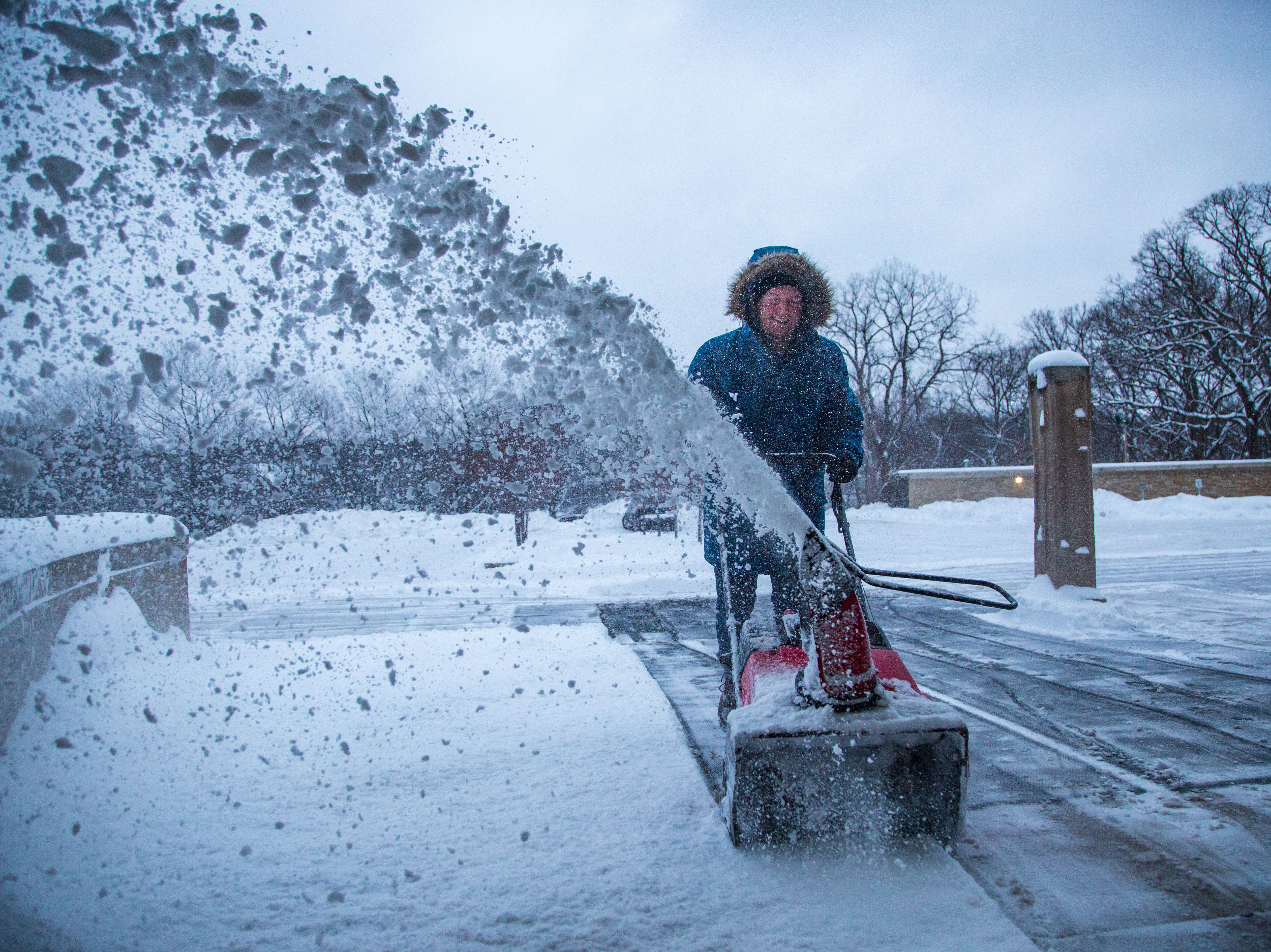 Matthew Lewin, facilities technician with the Des Moines Arts Center, clears a fresh blanket of snow Tuesday, Feb. 12, 2019.