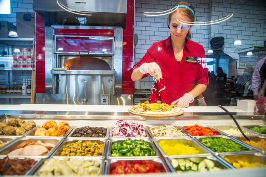 Molly Rhodes makes a pizza at the new Hy-Vee Fast and Fresh combination gas and grocery store in Altoona Tuesday, Feb. 12, 2019.