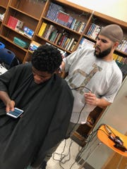 Local barber Nolan Clay cuts the hair of Justin, a member of the Meredith Middle School chapter of the Boys and Girls Clubs of Central Iowa, on February 6, 2019.