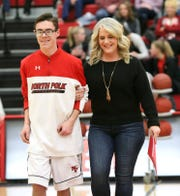 Clay Warner, 18, walks onto the North Polk High School basketball court with his mother, Melissa Warner, on Friday, Feb. 1,  2019, during the team's senior night.