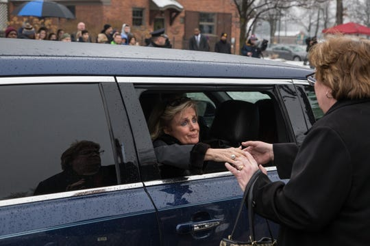 Rep. Debbie Dingell shakes the hand of a woman after loading into the limo to follow the hearse carrying her late husband former U.S. Representative John Dingell's casket at the end of his funeral at Church of the Divine Child in Dearborn on Tuesday, February 12, 2019.