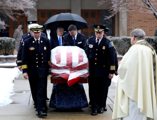 The casket of former Congressman John Dingell is taken by pallbearers towards the hearse at the Church of the Divine Child in Dearborn on Tuesday, February 12, 2019.