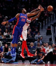 Detroit Pistons guard Wayne Ellington and Washington Wizards guard Jordan McRae reach for the inbound pass during the first half Monday, Feb. 11, 2019, in Detroit.