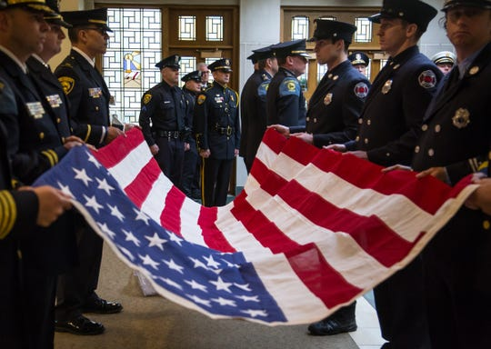 Officers stand guard while waiting to drape a flag on the casket of the late former U.S. Representative John Dingell at the end of his funeral at Church of the Divine Child in Dearborn on Tuesday, February 12, 2019.